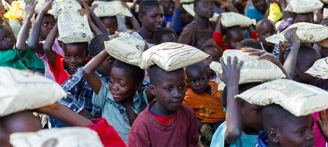 A group of underprivileged children carry bags of VitaMeal on their heads.