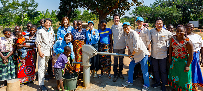 Nu Skin sales leaders and employees pose for a picture with locals from the village of Kasiya as they dedicate a new borehole water well to their village.