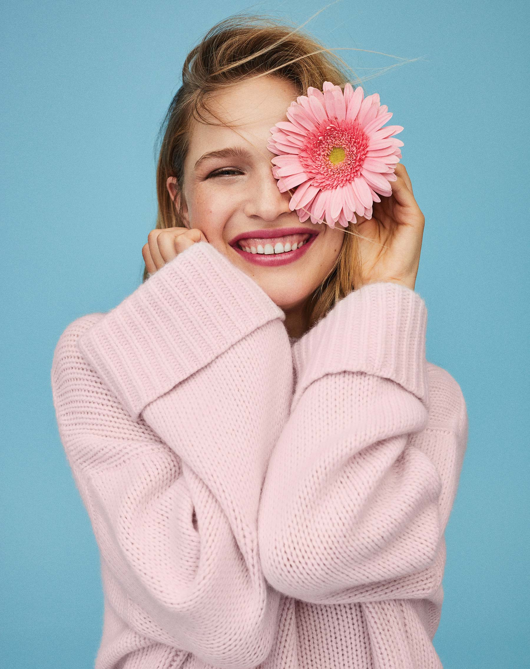 Youthful woman smiling and holding a flower over one eye