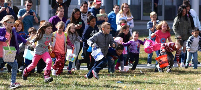 A group of kids running to collect Easter eggs at Nu Skin's annual East Egg Hunt