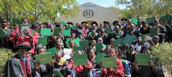 SAFI graduates hold their certificates up as they pose for a picture.