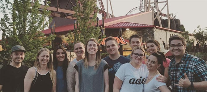 Nu Skin staff pose for a picture in front of the Cannibal roller coaster at Lagoon