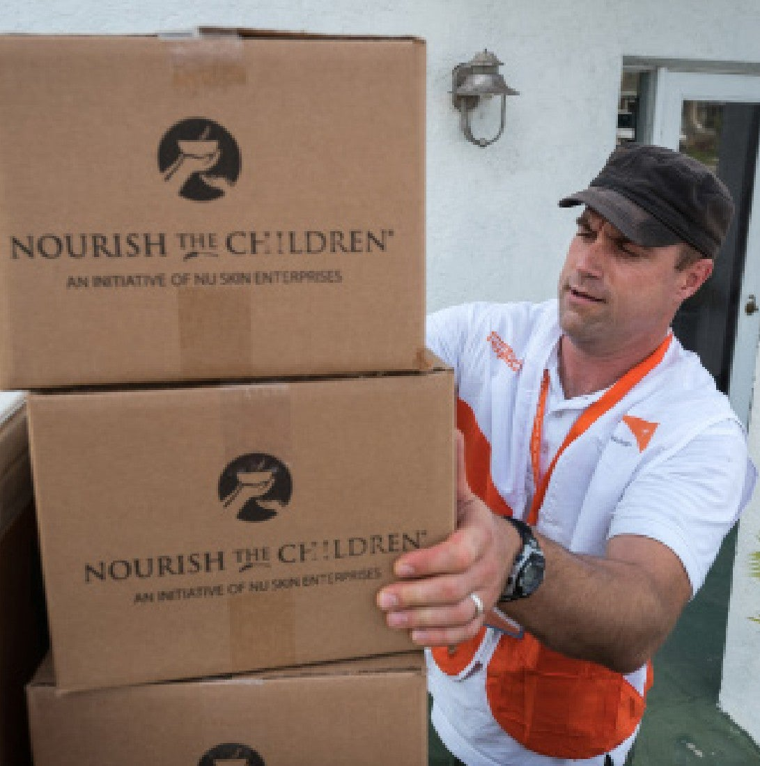 man preparing vitameal boxes for nourish the children