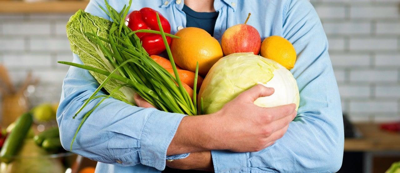 Hình ảnh người đàn ông đang ôm các loại hoa quả đầy dinh dưỡng